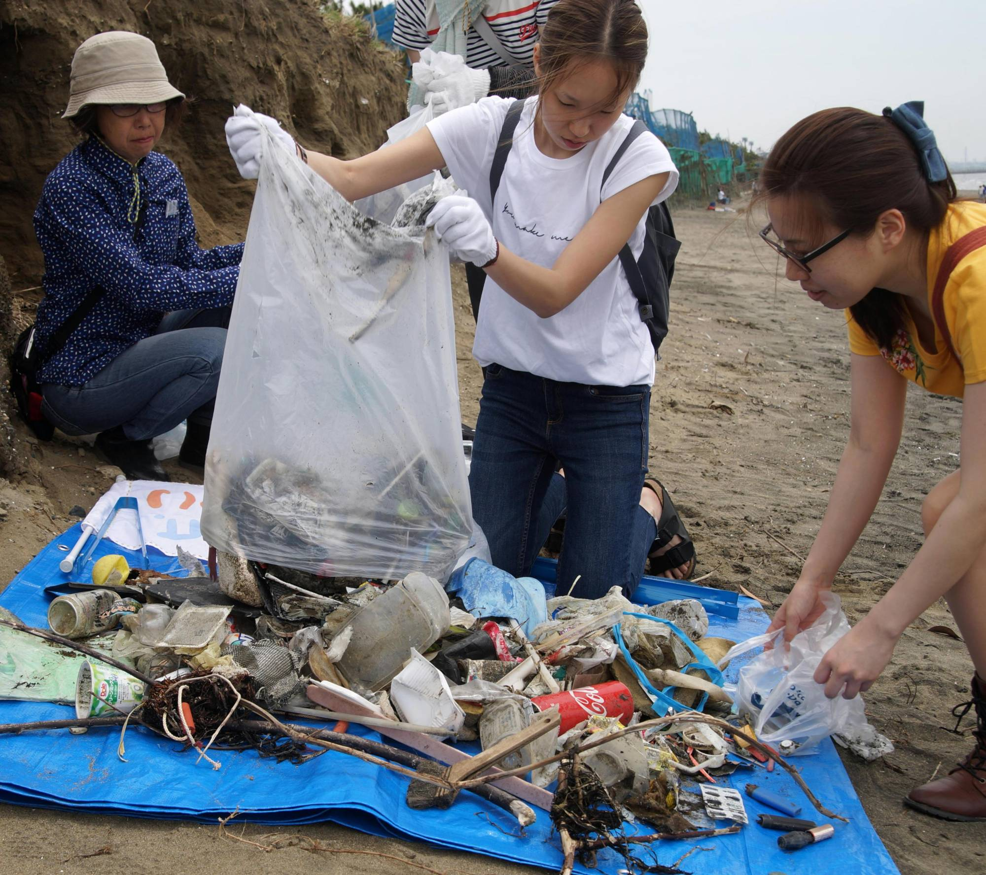 Volunteers collect waste, mostly plastic items, as they clean up beaches in the city of Chiba in May 2018. | KYODO