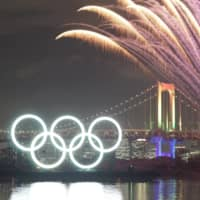 Fireworks explode above an illuminated Olympic sign during an event held in January to commemorate six months until the opening ceremony, which was originally planned to be held on Friday. It has since been postponed to next year amid the ongoing novel coronavirus pandemic. | RYUSEI TAKAHASHI