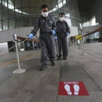 Workers spray disinfectant as a precaution against a new coronavirus at the National Museum of Korea in Seoul on Wednesday.  | AP
