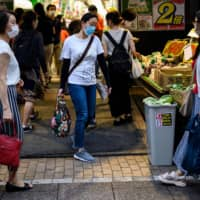 Customers shop at a supermarket in Tokyo on July 1. Many people in Japan are refraining from dining out amid the coronavirus pandemic. | AFP-JIJI