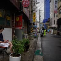 A man smokes a cigarette in Seoul on Wednesday. South Korea, Asia's fourth-largest economy, shrank by a seasonally adjusted 3.3 percent in the June quarter from three months earlier.  | AFP-JIJI
