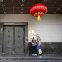 Visitors try to enter the Chinese Consulate in Houston on Wednesday. China says the U.S. order to close the facility is a provocation that violates international law. | AP