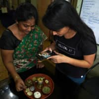 An Indian woman who used to post over a dozen videos on video-sharing app TikTok makes a video on her miniature cooking with her daughter on July 1.  | REUTERS