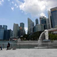 People sit near the Merlion statue in Singapore on April 2.    AFP-JIJI