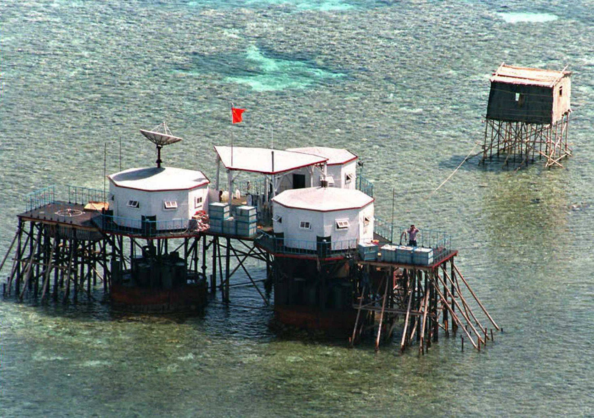 China's flag flies over newly built octagonal structures at Mischief Reef in the disputed Spratly Islands in 1995. U.S. Secretary of State Mike Pompeo announced July 13 that the United States would treat Beijing's pursuit of resources in the dispute-rife South China Sea as illegal. | AFP-JIJI