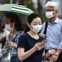 People walk in a street in Tokyo on Monday. According to environmentalists, Japanese coasts and waters have witnessed an apparent increase in the number of disposable masks recently. | AFP-JIJI