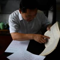 Yang Yiren, a Chinese naming expert at the Three-Arts Yijing Research Centre Beijing, gives a name to a man's newborn daughter at his office. Giving the mother's surname to a child is gaining traction in Chinese cities, defying deeply entrenched family traditions in the country.  | AFP-JIJI