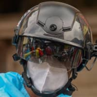 A volunteer health worker in a residential area in Mumbai looks through a smart helmet equipped with a thermo-scan sensor that can check body temperature. On July 17 India logged a million coronavirus cases, the third-highest total in the world. | AFP-JIJI