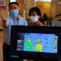 A woman has her temperature checked to avoid the spread of the coronavirus at the Sejong Center for the Performing Arts in Seoul on Tuesday.  | REUTERS