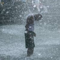 A man cools off in splash pad at Washington Square Park in New York City on Saturday.  | BLOOMBERG
