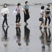 People wearing face masks walk on a beach in Fujisawa, Kanagawa Prefecture. Including Kanagawa, prefectures in the Tokyo metropolitan area have recently seen rises in the number of COVID-19 cases.   AP
