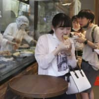 People eat dumplings in Yokohama's Chinatown on Friday. More than 770 infections were reported nationwide, including a record high in Osaka.   AP