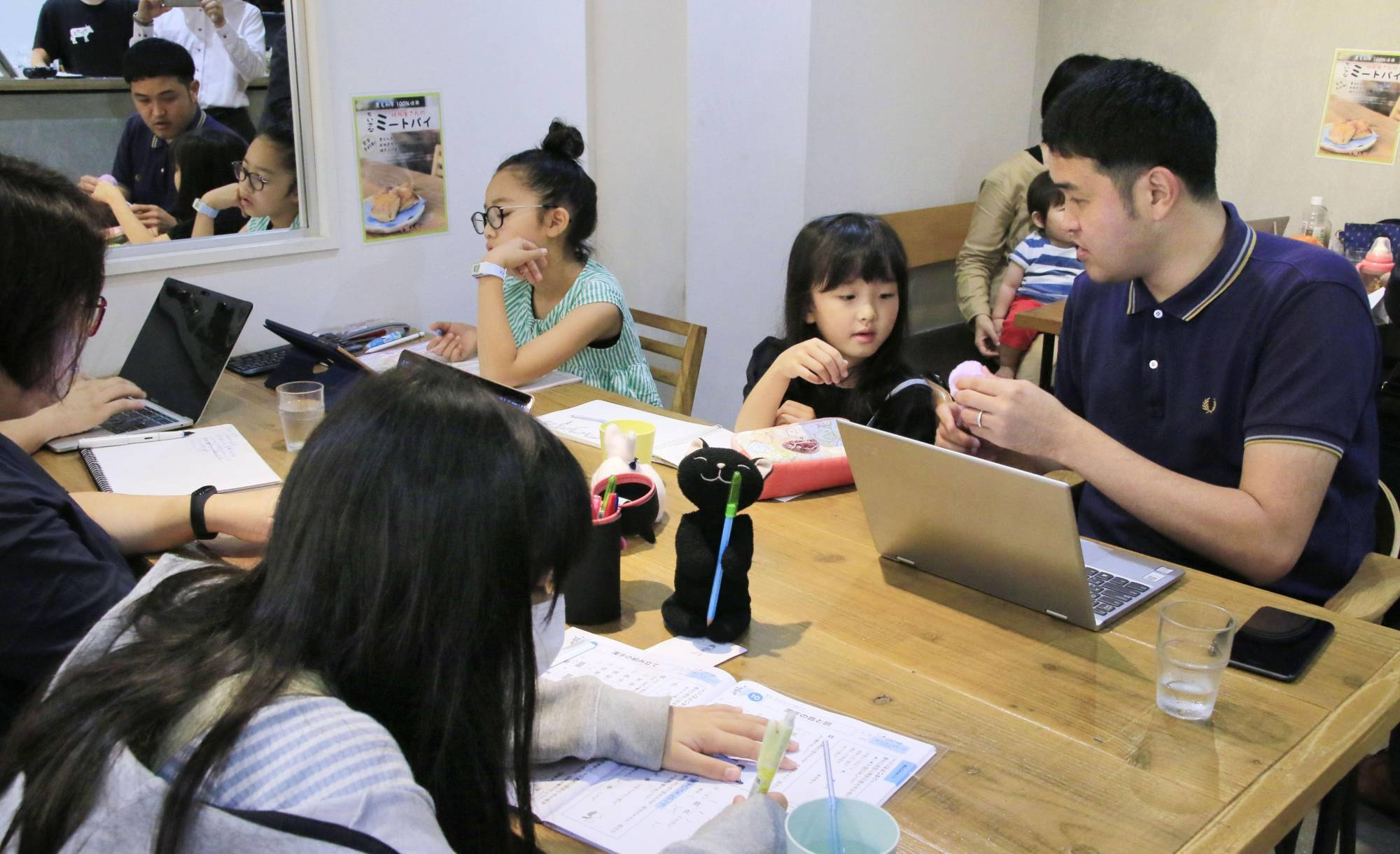People participate in a demonstration for promoting child care during remote work at a cafe in Tokyo in July 2019. | KYODO