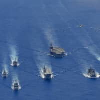 The USS Ronald Reagan Carrier Strike Group and units from the Maritime Self-Defense Force and Australian Defense Force participate in trilateral exercises in the Philippine Sea, on the doorstep of the disputed South China Sea, earlier this week. | U.S. NAVY