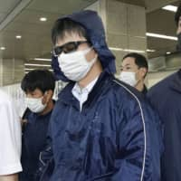 Naoki Yamamoto (center), a doctor in Tokyo who was arrested on suspicion of helping a woman die, arrives at Kyoto Station on Thursday. | KYODO