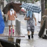 People walk in heavy rain in the Kumamoto Prefecture city of Hitoyoshi on Friday. | KYODO