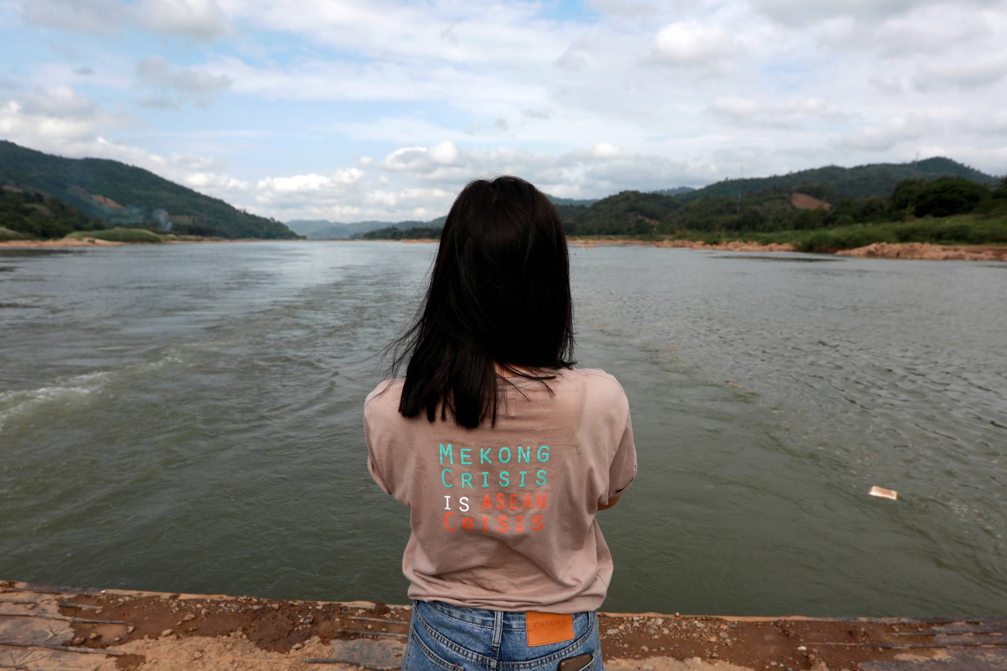A woman stands next to the Mekong River bordering Thailand and Laos. The state of the Mekong is an urgent worry for the 60 million people who depend on it for farming and fishing as it flows from China through Southeast Asia.  | REUTERS