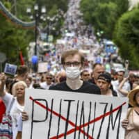 A man holds poster reading 'Putinizm ' during a protest in Khabarovsk, Russia, on Saturday.   AP