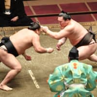 Yokozuna Hakuho (right) battles Kiribayama on the seventh day of the July Grand Sumo Tournament on Saturday. | NIKKAN SPORTS