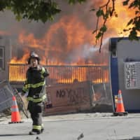 A construction site burns near the King County Juvenile Detention Center in Seattle on Saturday. | AP