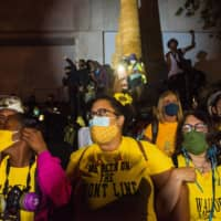 Members of the Portland Mom Brigade link arms as they take part in a rally against police brutality in Portland, Oregon, on Friday. | AFP-JIJI