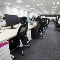 Employees toil in a nearly empty office in Tokyo in July as the COVID-19 outbreak pressures more people to work from home. | KYODO