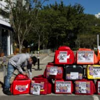A man is seen next to food delivery bags as Brazilian delivery workers for Uber Eats, Rappi and other delivery apps protest as part of a strike to demand better pay and working conditions amid the coronavirus disease outbreak, in Sao Paulo, Brazil, on Saturday.     REUTERS