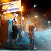 Police use water cannon during a protest against Israeli Prime Minister Benjamin Netanyahu's alleged corruption and his government's handling of the coronavirus disease crisis, near his residence in Jerusalem on Sunday.   REUTERS