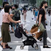 Pedestrians cross a street in Tokyo's Ginza shopping district on Saturday. | AFP-JIJI