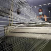 A worker wearing a protective face mask works on a loom in a textile factory, amidst the coronavirus disease outbreak, in Meerut, India, on July 7. | REUTERS