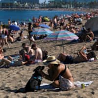 People enjoy the sunny weather at Barceloneta beach, after Catalonia's regional authorities and the city council announced restrictions to contain the spread of the coronavirus disease in Barcelona, Spain, on July 19. | REUTERS