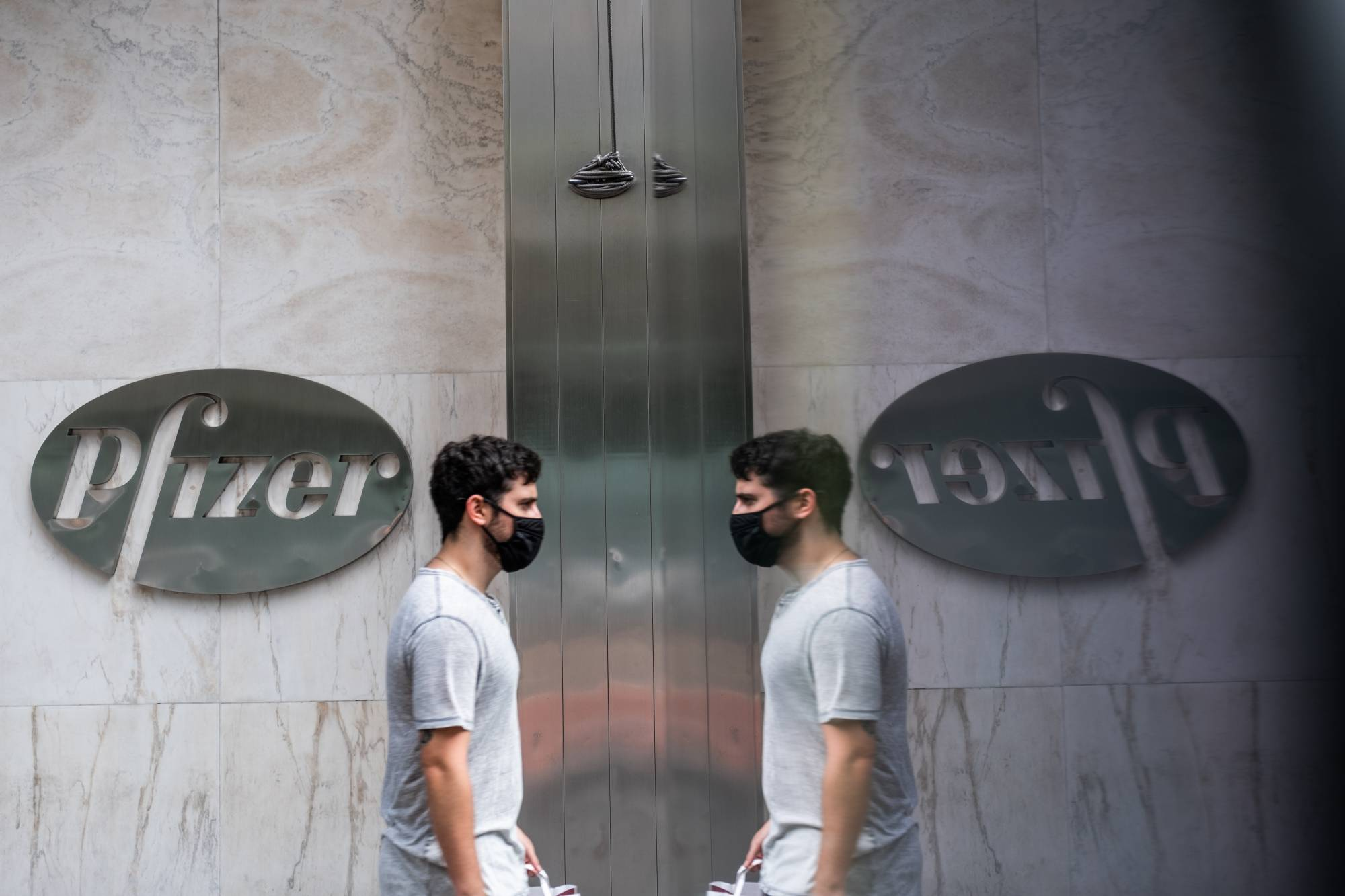 A man passes in front of Pfizer Inc.'s headquarters in New York on July 22. U.S. health officials agreed pay $1.95 billion for 100 million doses of a vaccine made by Pfizer Inc. and BioNTech SE. There are more than 160 coronavirus vaccines in development, according to the World Health Organization, though only 25 are currently in human studies. | BLOOMBERG