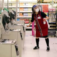 An employee wearing a protective mask and face shield uses an alcohol-based solution to clean automated checkout counters in an Aeon shopping mall in Chiba on May 28. | REUTERS