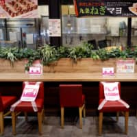 Social distancing signs tell shoppers where they shouldn't sit in a dining area in an Aeon shopping mall in Chiba on May 28. | REUTERS