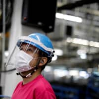 An employee with a protective mask and face shield works on the assembly line at the Mitsubishi Fuso Truck and Bus Corp. factory in Kawasaki on May 18. | REUTERS