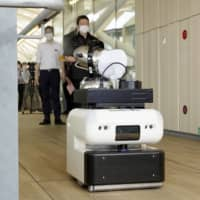 A cleaning robot sprays disinfectant at Takanawa Gateway Station in Tokyo on Monday. | KYODO