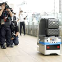 A robot carries luggage at Takanawa Gateway Station in Tokyo on Monday. | KYODO