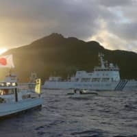 Chinese marine surveillance ships and Japan Coast Guard vessels and a Japanese fishing boat sail near Uotsuri Island on July 1, 2013. | KYODO