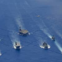 The Ronald Reagan Carrier Strike Group and units from the Maritime Self-Defense Force and Australian Defence Force participate in trilateral exercises in the Philippine Sea last week. | U.S. NAVY