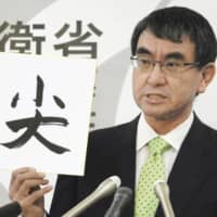 Defense Minister Taro Kono holds up a sign with the first kanji character for the word Senkaku at the Defense Ministry last December. | KYODO