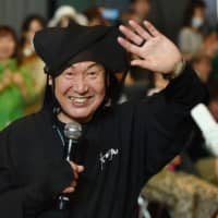 Kansai Yamamoto waves to the audience after an event in Tokyo on June 12, 2015. | AFP-JIJI