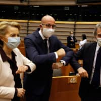 European Commission officials celebrate on Thursday what they boasted was a historic rescue plan for EU economies left shattered by the coronavirus epidemic. | AFP-JIJI