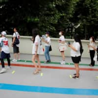 Fans wearing face masks as a measure to prevent the spread of the new coronavirus wait in line to get into a KBO baseball game  at a stadium in Seoul on Sunday. | REUTERS