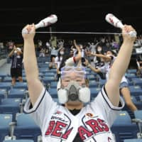 A fan wearing a face mask to help protect against the spread of the new coronavirus cheers during the KBO game in Seoul on Sunday. | AP