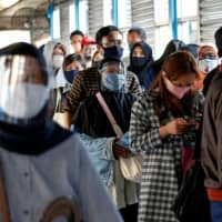 Passengers line up for a bus in Jakarta on Monday.  | REUTERS