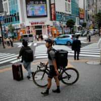 Takenobu Tonegawa has taken on additional work, as a part-time delivery driver for Uber Eats, due to a decline in business for his video production firm.   REUTERS