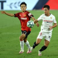 Mallorca's Takefusa Kubo (left) vies for the ball with Sevilla midfielder Olivier Torres during a July 12 game in Seville. | AFP-JIJI