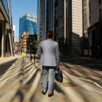 A businessman walks to work in a deserted City of London on July 20. Employers and employees increasingly see offices as an option rather than a necessity for many white-collar workers.   BLOOMBERG
