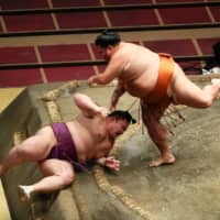 Mitakeumi (right) defeats Asanoyama with an overarm throw on Tuesday at Ryogoku Kokugikan, handing the ozeki his first defeat of the July Basho. | NIKKAN SPORTS