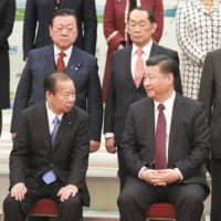 Toshihiro Nikai (left, front), the Liberal Democratic Party's secretary-general and Chinese President Xi Jinping at the Great Hall of the People in Beijing in December 2017. | KYODO